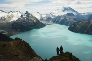 Couple embracing at a stunning vantage point overlooking a glacial lake in British Columbia, Canada's Coast Mountain Range.